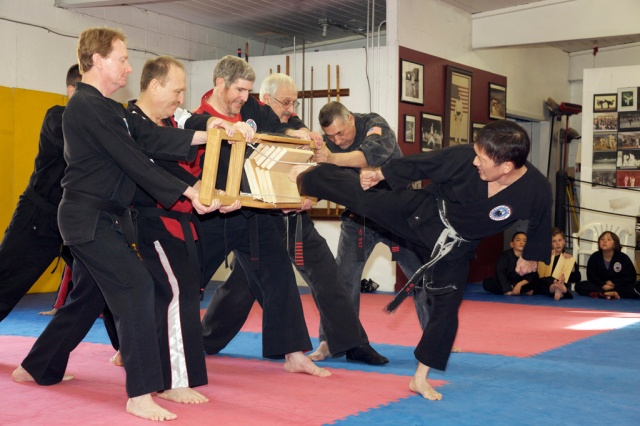 Master Kim breaking with a back kick.